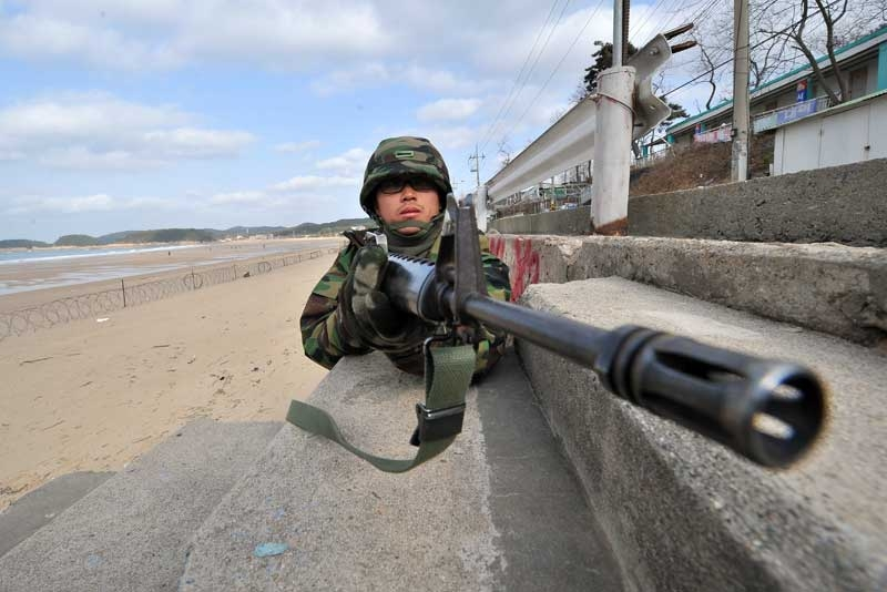 A South Korean soldier stands guard as others prepare for landing operations on a beach in Taean, around 170 km southwest of Seoul on November 28, 2010. The US and South Korea staged a potent show of naval strength as residents of a border island bombarded last week by North Korea scurried for shelter for fear of a new attack. (Jung Yeon-Je/AFP/Getty Images)
