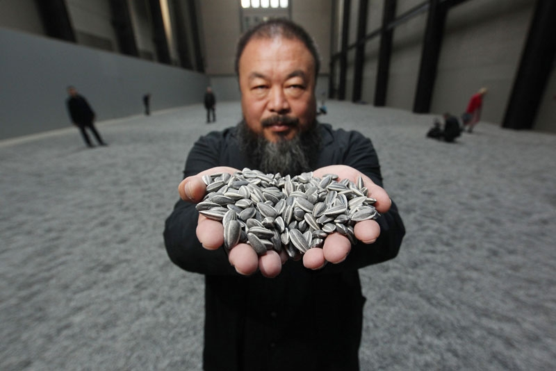 Chinese artist Ai Weiwei holds some porcelain sunflower seeds from his installation at The Tate Modern in London on October 11, 2010. (Peter Macdiarmid/Getty Images)