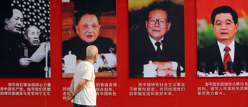 An elderly man looks at portraits of former Chinese communist leaders (L to R) Mao Zedong, Deng Xiaoping, Jiang Zemin and current president Hu Jintao in Ditan Park in Beijing on June 28, 2011. (Peter Parks/AFP/Getty Images)