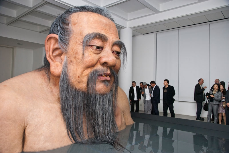 Visitors to the Rockbund Art Museum in Shanghai, China, react to a sculpture of Confucius by artist Zhang Huan. (Rockbund Art Museum)