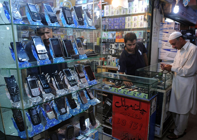 A Pakistani mobile seller shows phones to a customer at a Lahore electronics market in 2010. As of late 2011, Pakistan is estimated to have 100 million cell phone users. (Arif Ali/AFP/Getty Images)