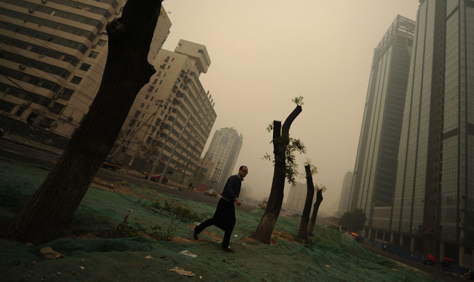 A man walks through heavy pollution on a street in Beijing. (Peter Parks/AFP/Getty Images)