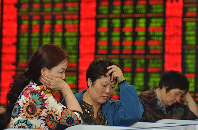 Investors check share prices in a stock firm in Fuyang, China on June 29, 2015. (STR/AFP/Getty Images)