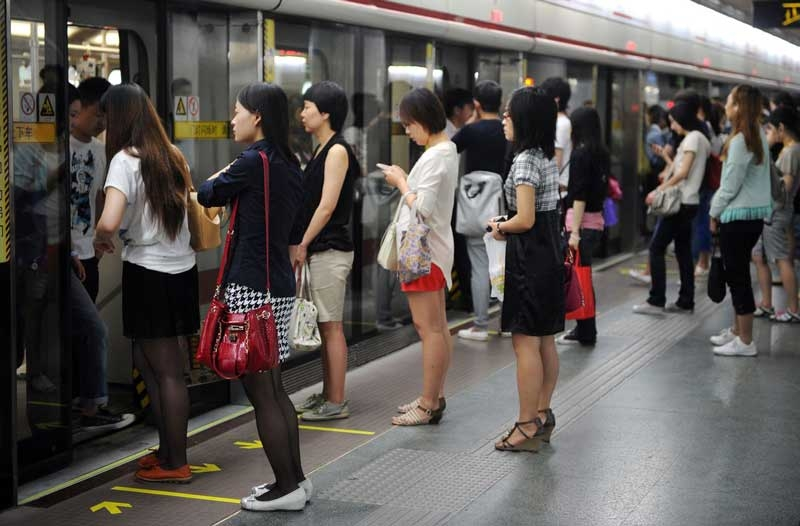 Passengers wait in line to board a subway train in Shanghai on June 27, 2012. (Peter Parks/AFP/Getty Images)