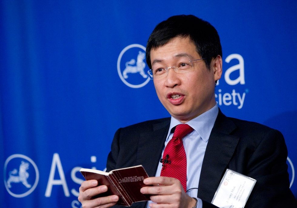 Johnny Mok, Senior Counsel for Hong Kong SAR, references a pocket-sized version of the Basic Law during a June 27, 2014 lunch at Asia Society New York. (Elena Olivo/Asia Society)