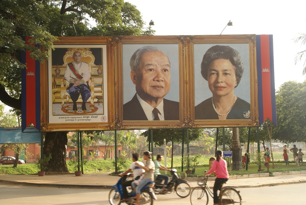 Cambodia's royal family is revered across the country with huge posters, as show in this photo taken in Siem Reap Province in November 2007. L to R: the current King Norodom Sihamoni, Norodom Sihanouk, and the Queen Mother. (Patrik M. Loeff/Flickr)
