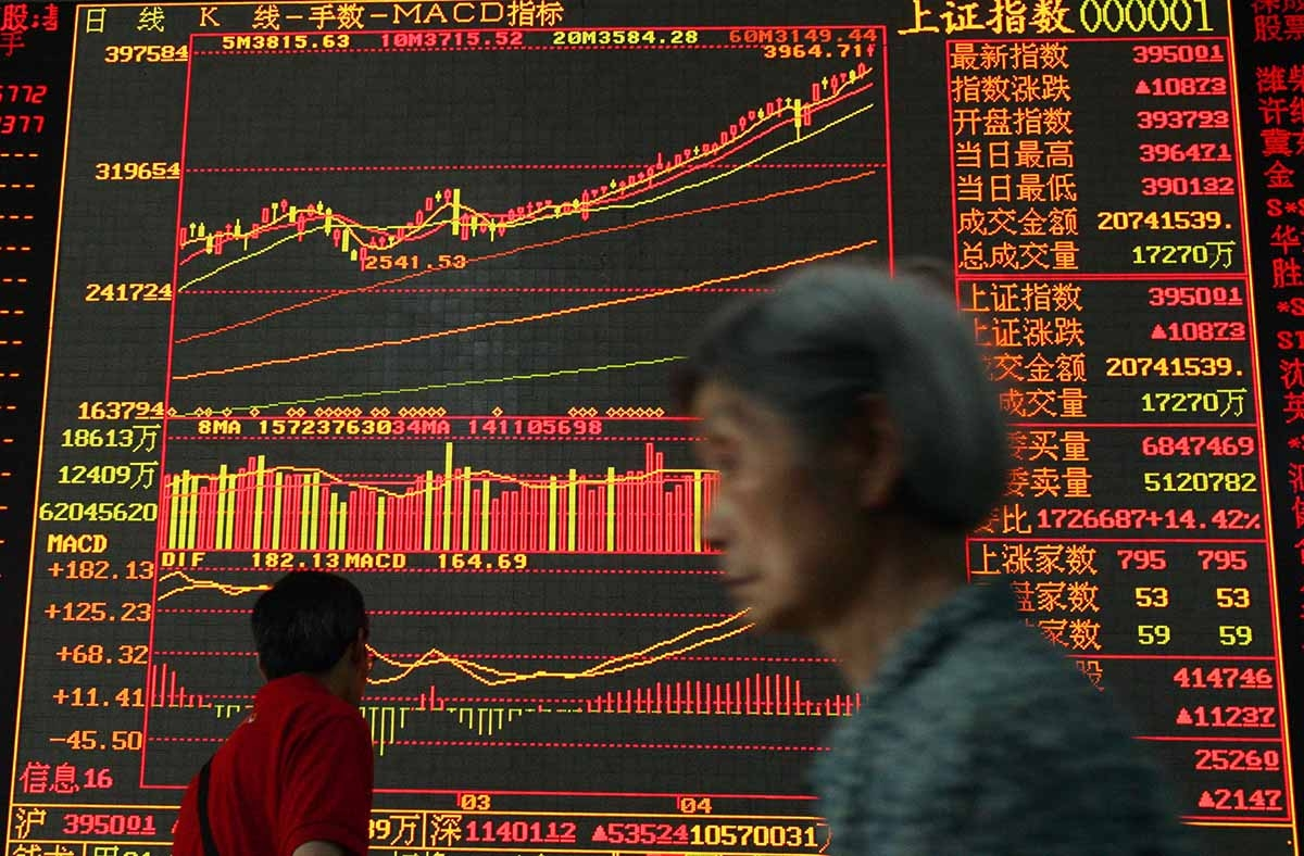 An investor walks past an electronic screen displaying stock index at a securities company in Wuhan, China. (China Photos/Getty)