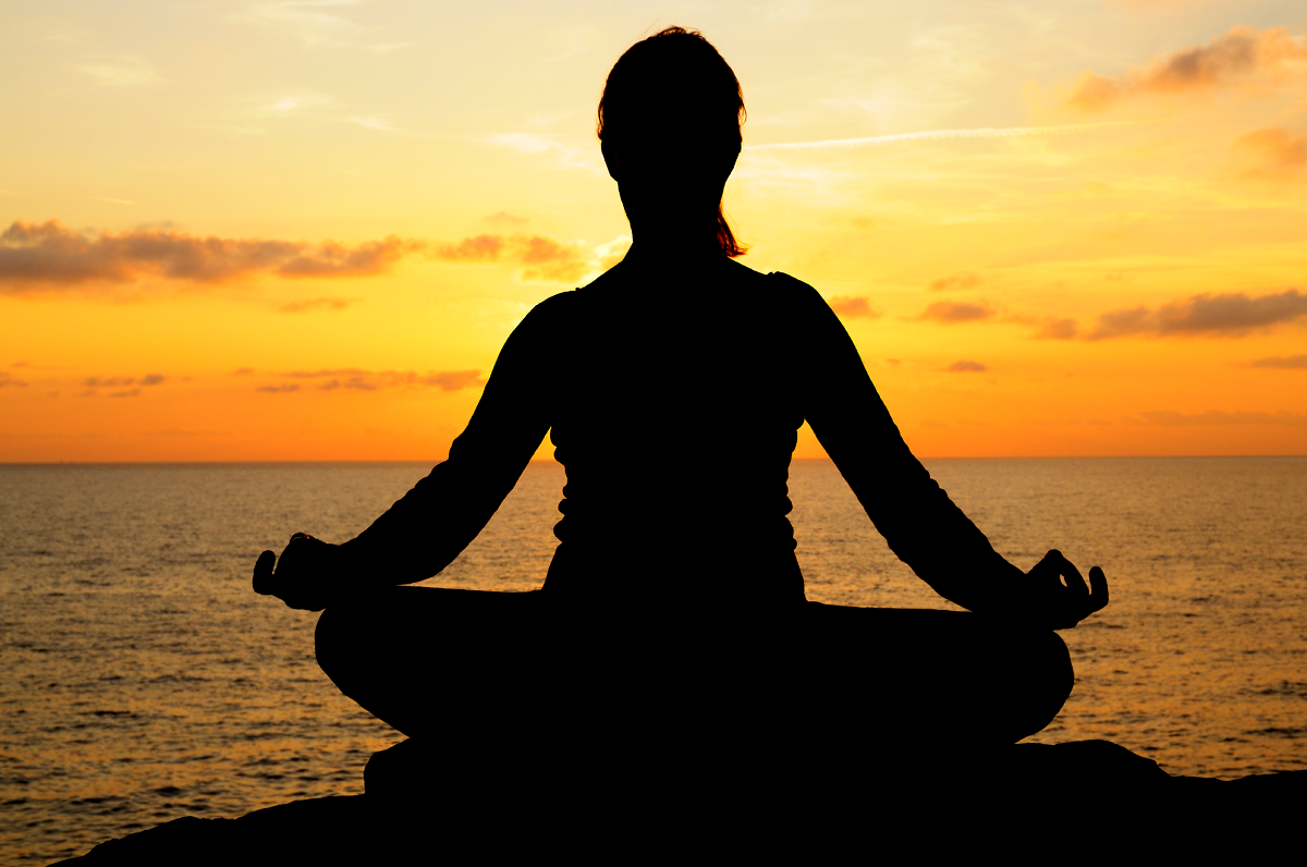 A woman meditating facing the sunset