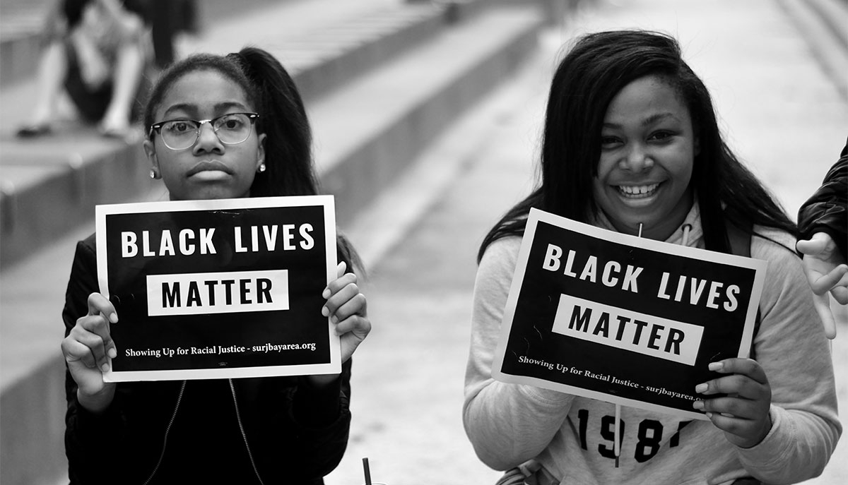Two people hold Black Lives Matters signs at a protest (Tom Hilton/Flickr)
