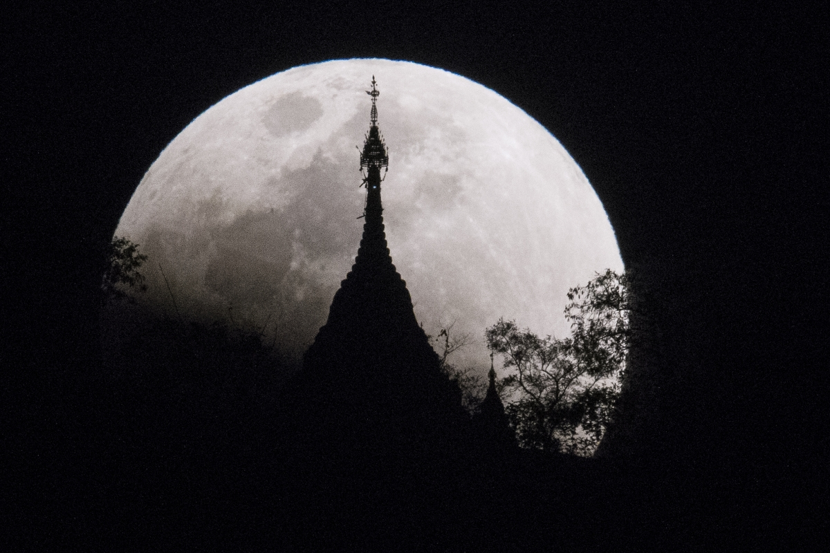 The moon rises over a pagoda in Kumal, Myanmar