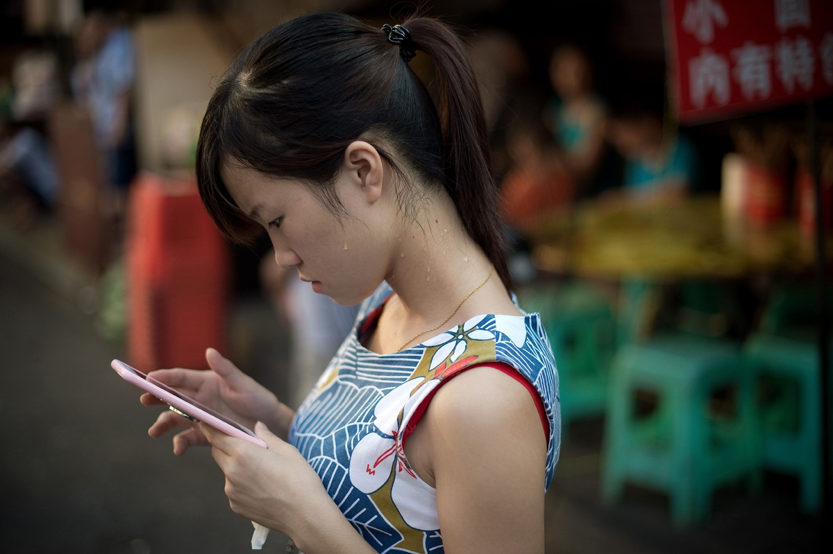 A woman examines her phone in Chongqing, China.