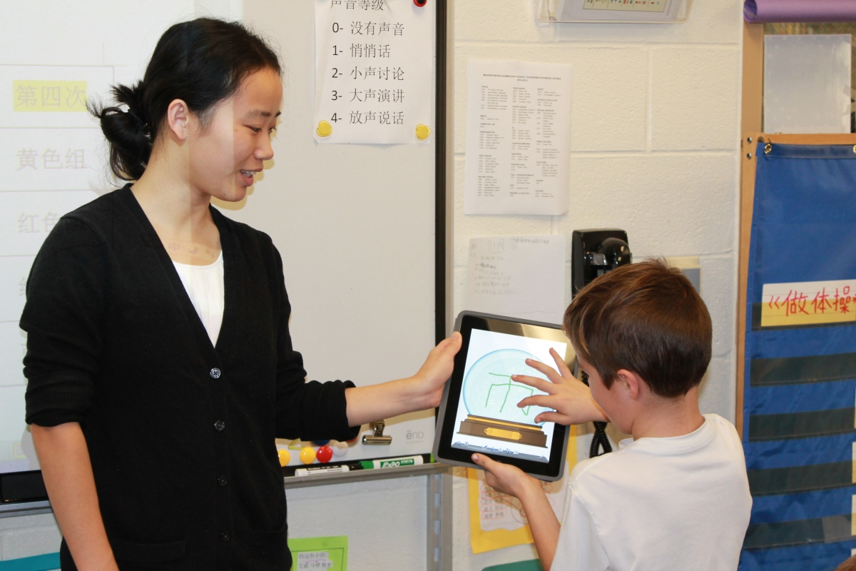 A student works with his teacher to write the appropriate Chinese character on an electronic tablet.