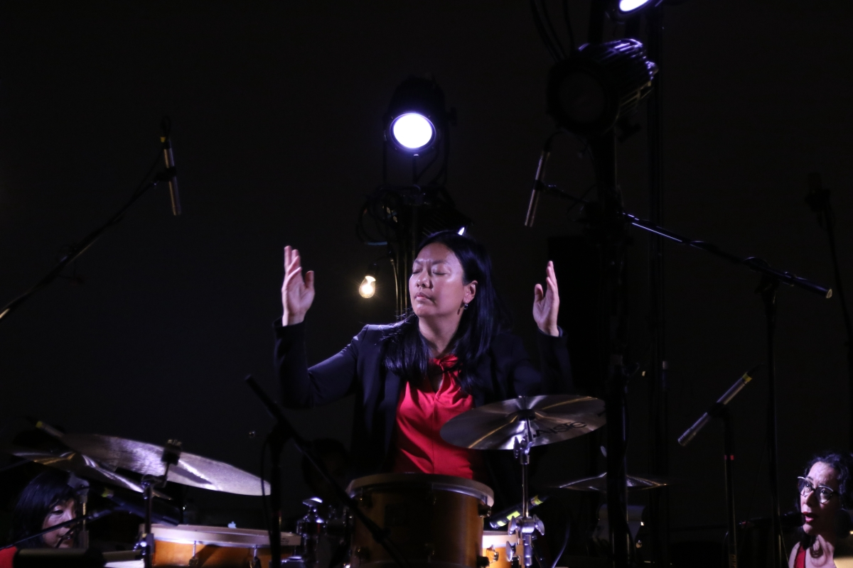 Drummer and composer Susie Ibarra conducting. She is wearing a red top and black blazer.