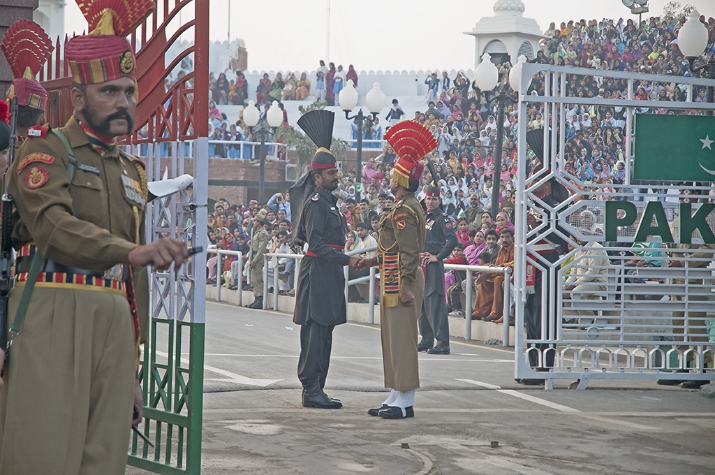 Indian and Pakistani guards shake hands at the Wagah border