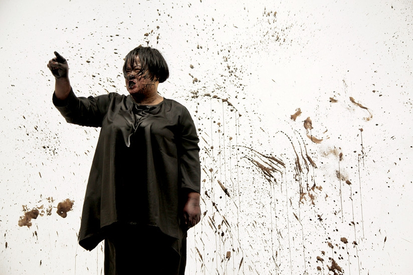 Performance artist Melati Suryodarmo stands covered in black ink with her right finger pointed upwards.