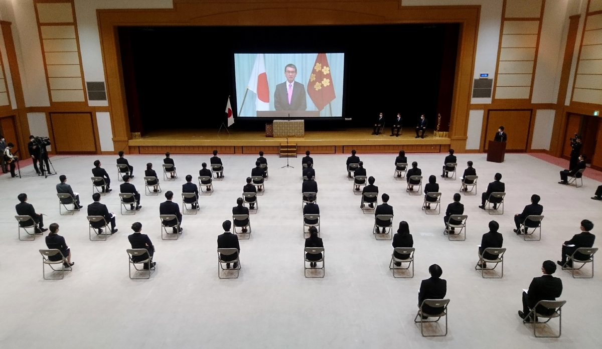 New defense ministry employees listening to Defense Minister Taro Kono speak via video and spread out due to COVID-19.