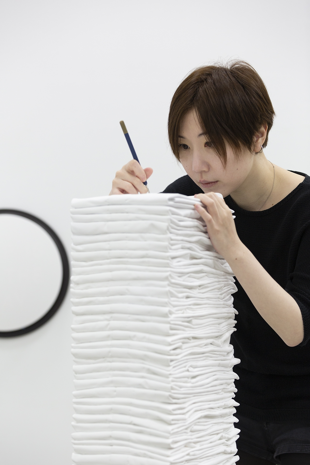 A person wearing a dark t-shirt leans on top of a stack of folded white fabric. She holds a pencil and uses it to mark the top of the fabric