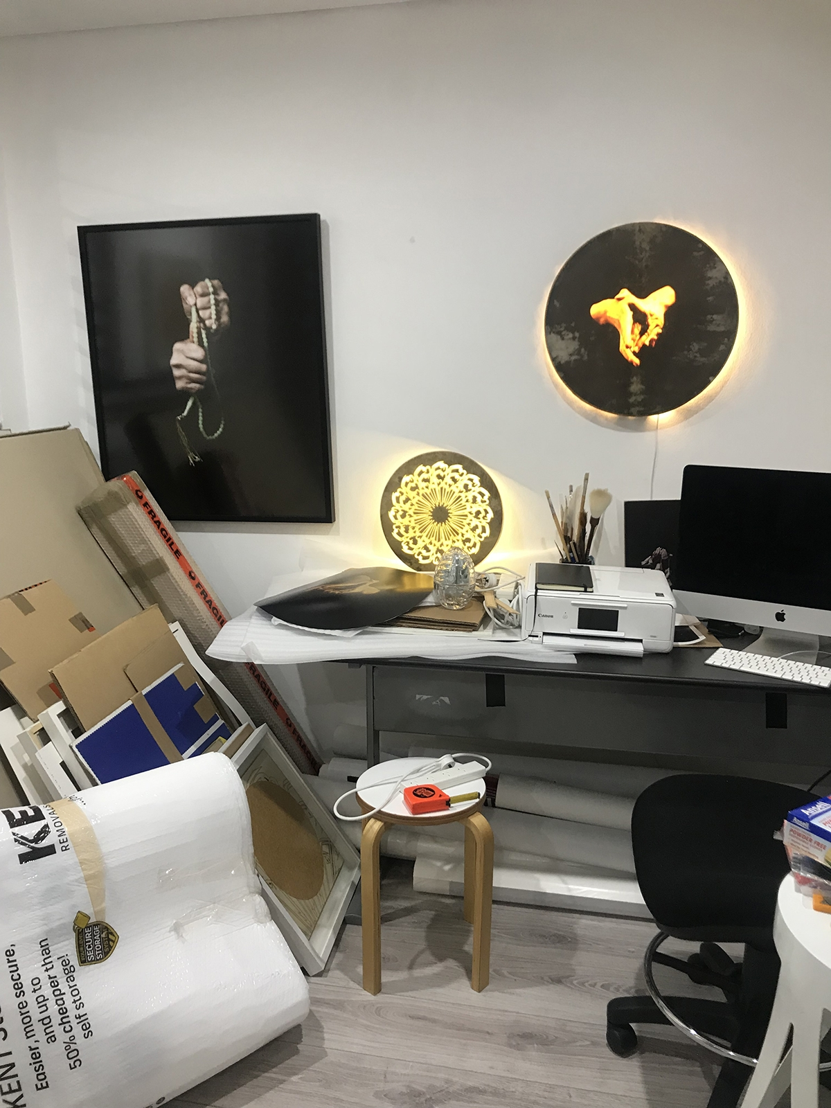 A framed photograph of hands, a stack of cardboard, an illumanited graphic artwork, a computer screen, and a stool are among the items seen in a white room.