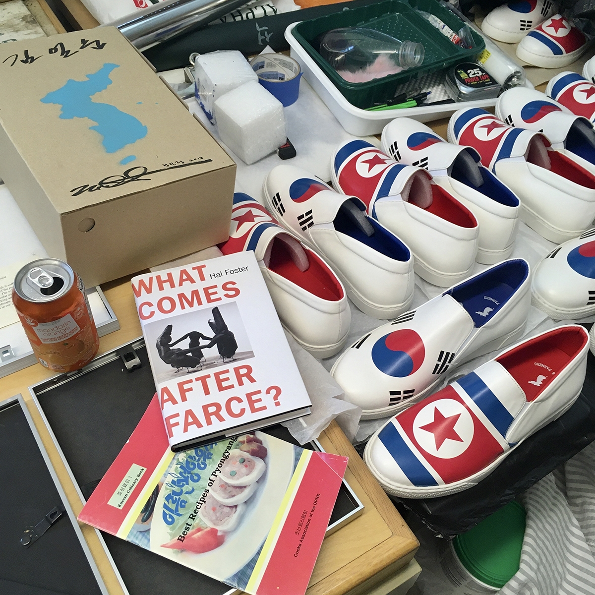 An orange aluminum can, a book by Hal Foster, a cookbook, and many pairs of white slip on shoes with the North and South Korean flags appear on a surface.