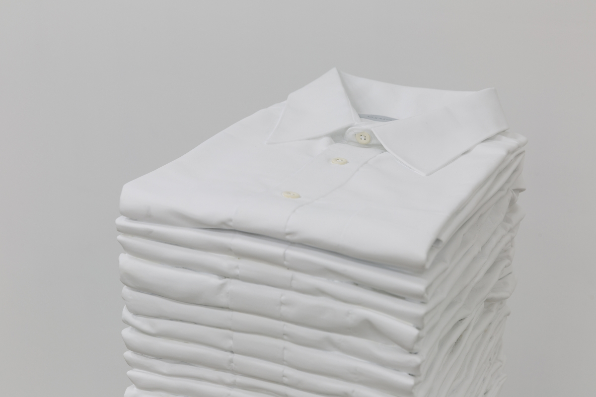 A stack of folded white collared shirts in front of a white background