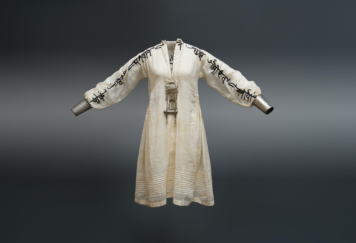 A long sleeved white gown with embroidery down both sleeves and an silver chain with pendant hanging from the neckline