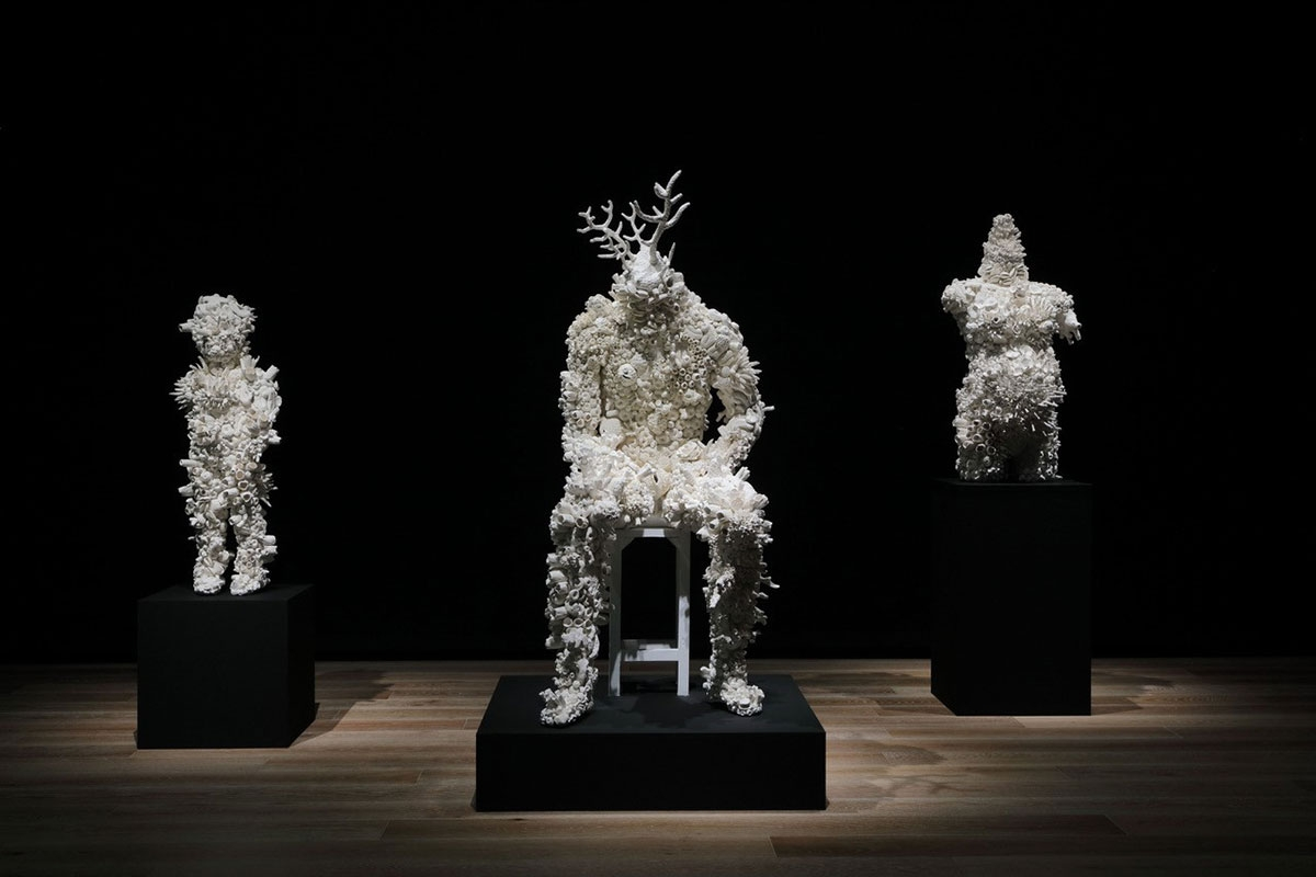 Three figurative sculptures appear on individual black plinths. Each is sculpture is composed of creamy white biomorphic forms that resemble coral.