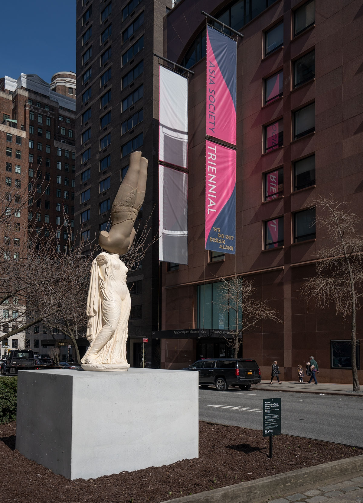A plinth appears on a median outside of Asia Society Museum. On it is a sculpture composed of two casts: on top an inverted bronze-colored eleventh-century male figure from Cambodia, balanced atop a light beige cast of a second-century Roman figure of Venus Genetrix. Neither figure has a head.