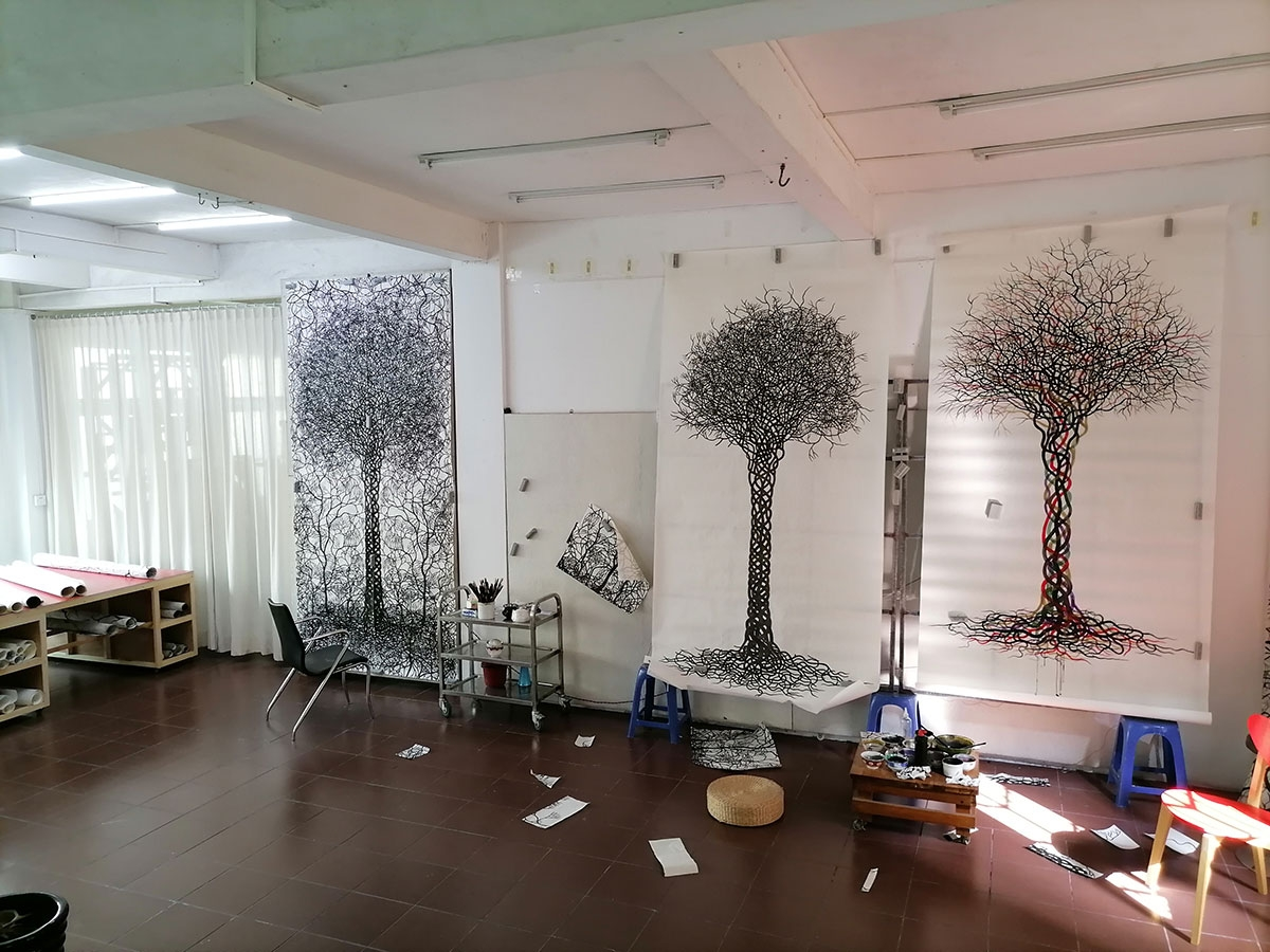 A photograph of the artist's studio. Three large, vertical sheets of paper are hung up; each features an intricately drawn tree with hundreds of interlaced branches and roots. A chair, drafting table, rolls of paper, paints, and paintbrushes are visible.
