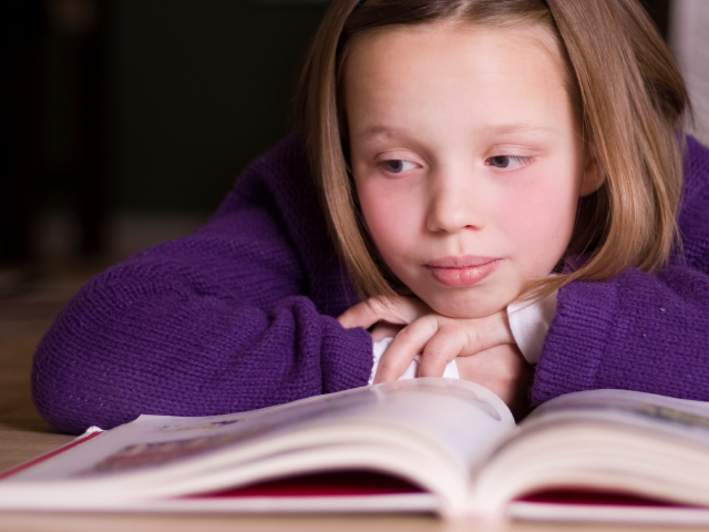 Girl reading book. (alexandercreative/istockphoto)