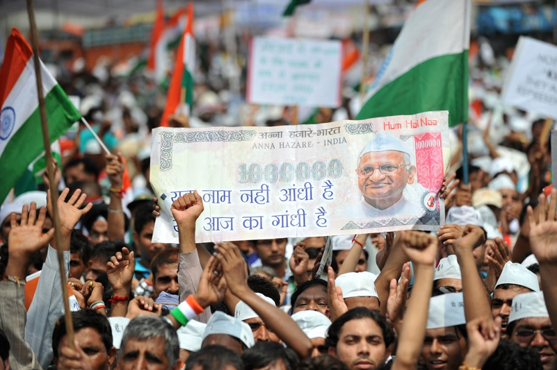 Supporters of the anti-corruption hunger strike by Indian activist Anna Hazare wave the national flag and hold up a fake Indian currency note depcting a portrait of Hazare during a rally in New Delhi on August 21, 2011. (Sajjad Hussain /AFP/Getty Images)