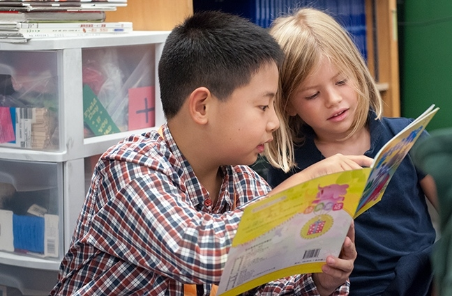 Visiting student from Renmin Primary School in Chongqing reads to Mandarin Immersion kindergartener at Beacon Hill International School.