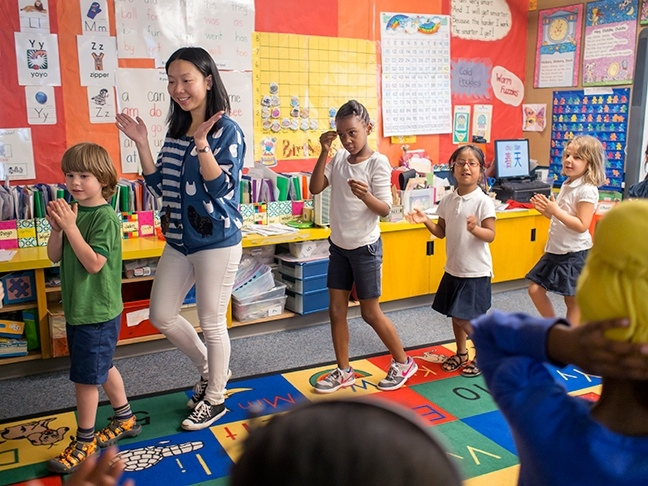 Visiting teacher from Chongqing engages kindergardeners in song and movement as they learn Chinese language at Beacon Hill International School.