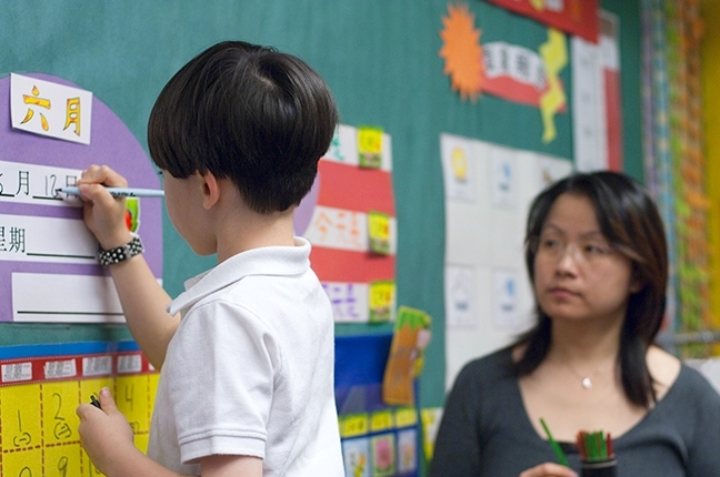 In 1st grade Mandarin Immersion a selected student fills in the daily calendar.