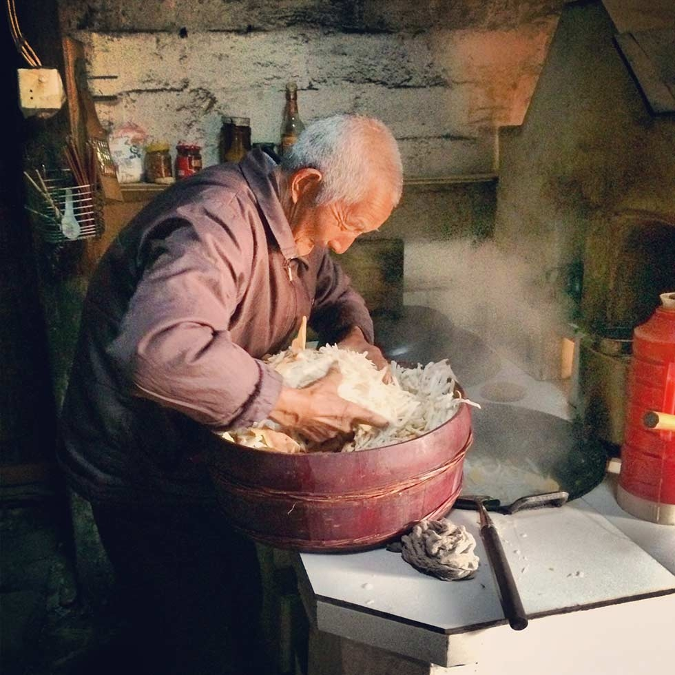 A villager cooking shredded sweet potato and daikon for his pig. As the Spring Festival approaches, households race against time to make their pigs gain more weight before they are to be slaughtered in time for new year's eve. (Sun Yunfan)