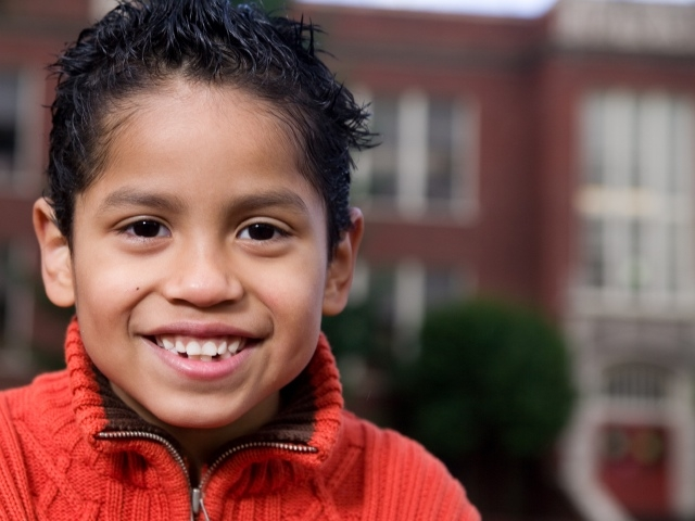 A child smiles in front of a school building.