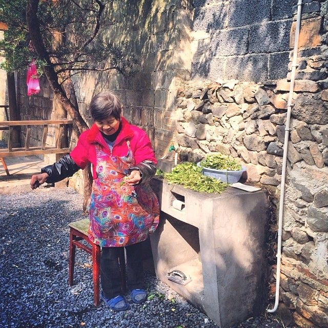 Chen Xueping, mother of Ou Ning, washing spinach in the back yard. (Sun Yunfan)