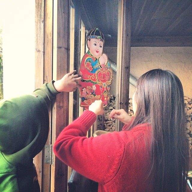 Tang Xue, Ou Ning's fiance, decorates a window in their home to bring good luck for the new year. (Sun Yunfan)