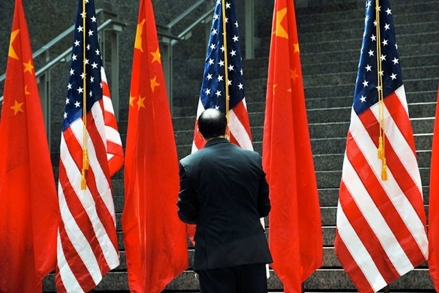 An official adjusts Chinese and US flags during the US-China Strategic and Economic Dialogue, held July 27, 2009 in Washington, DC. (Jewel Samad/AFP/Getty Images)
