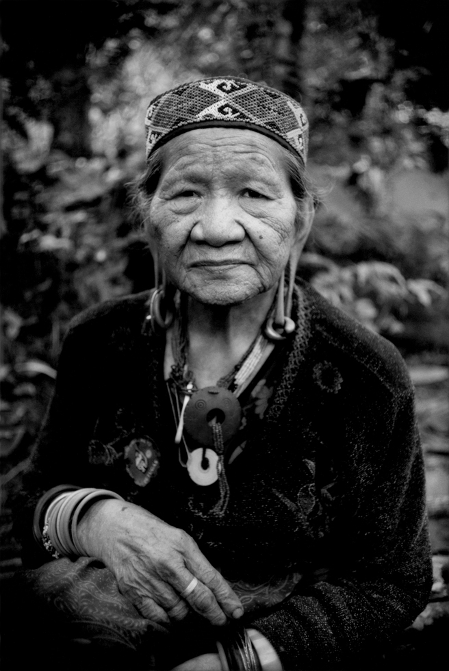 An traditional aged Penan woman in Long Kepang, Malaysia, sits in the rainforest, which is only accessible on foot.  (James Whitlow Delano)