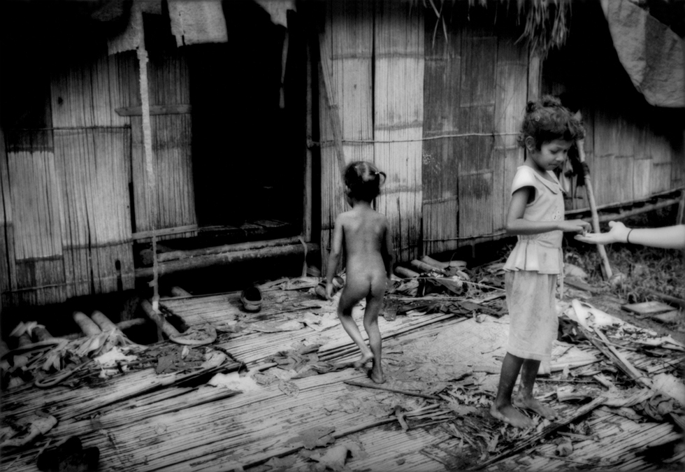 Batek Negrito girls living in poor conditions in the settlement built by the government to lure them out of the rainforest. (James Whitlow Delano)