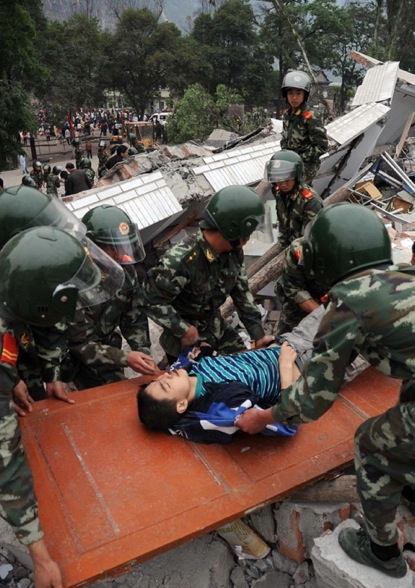 Chinese rescuers evacuate a boy from the rubble of a collapsed building in Beichuan on May 13, 2008, after an earthquake measuring 7.8 rocked southwest China's Sichuan province.