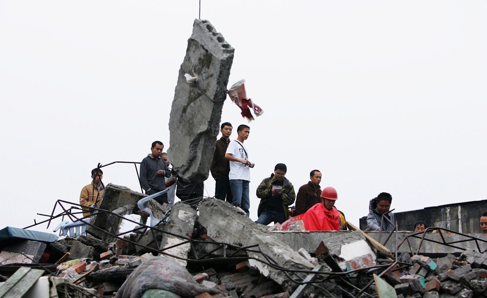 Residents watch soldiers rescue people from a ruined building in Sichuan province's Dujangyan City on May 13, 2008. (Guang Niu/Getty Images)