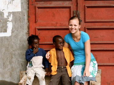 Student studying abroad, posing with children. (Miss Hibiscus / istockphoto)