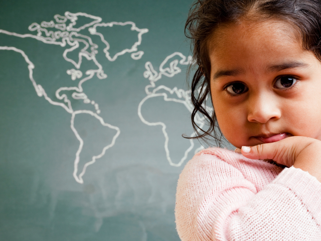 A child sits in front of a chalkboard map of the world.
