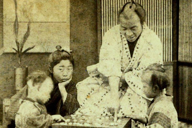 "A father teaches his kids the game of ""Go"" in Old Japan. (Okinawa Soba/flickr)"