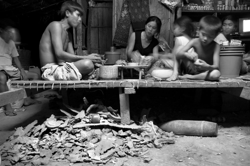 Family eating dinner above shrapnel, UXO, and bomb casings (Jerry Redfern)