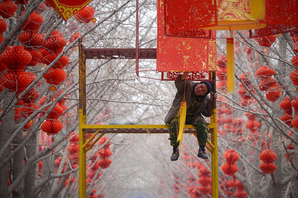 A worker puts the finishing touches on lantern decorations for Spring Festival celebrations at a park on January 24, 2014 in Beijing, China. (Wang Zhao/AFP/Getty Images)