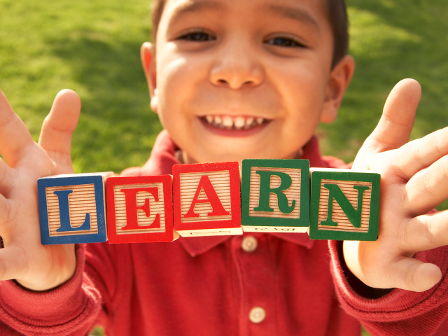 A child with blocks spelling LEARN. (marsbars/istockphoto)