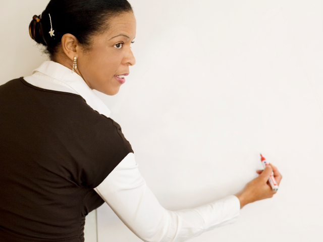 A teacher writes on a whiteboard (sunara/istockphoto)