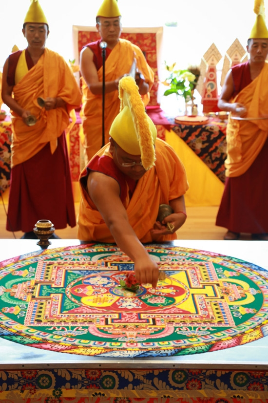 The monks sweep up the mandala's colored sands during the closing ceremony (Jessica Ngo)